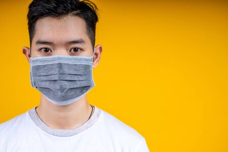 Young asian man in whit t-shirt wearing medical mask on isolated yellow background. Coronavirus or covid-19 protection concept.