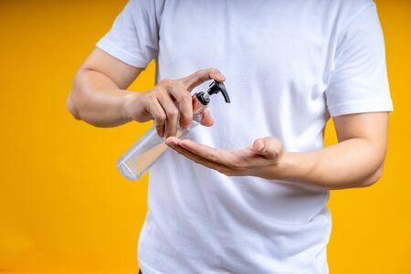 Asian man washing hands with alcohol gel or hand sanitizer over yellow isolate background. Man using bottle of antibacterial sanitiser soap. Coronavirus or COVID-19 prevention concept.