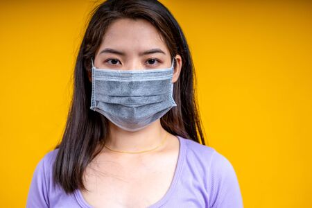 Young Asian woman wearing mask over yellow background. Corona virus or covid-19 concept.