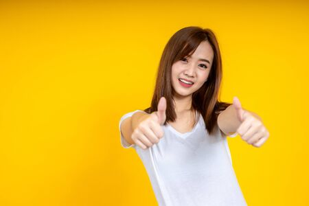 Close up of young Asian woman isolated on yellow background showing thumps up with positive emotions of content and happiness. Copyspace, concept of satisfaction with quality and recommendation. Stockfoto