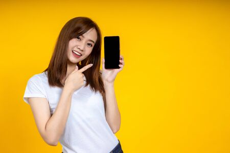 Smiling young Asian woman is pointing on smartphone standing on yellow background. Stockfoto