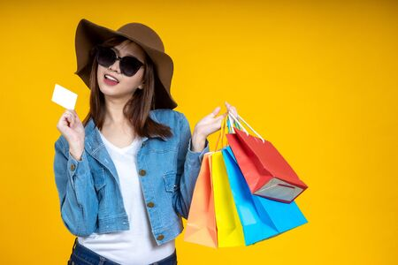 Portrait of Asian woman nice attractive wearing sun glasses carrying new shopping bag showing a credit card on bright isolated yellow color background. Shopping concept. Stockfoto