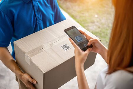 A young Asian deliveryman is delivering a package of women in front of her house. And asked her to scan the QR code after she made an online order during the coronavirus or Covid-19 virus outbreak.