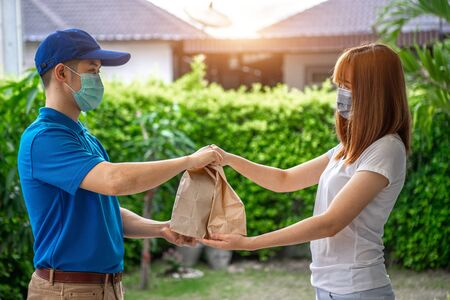 Asian deliveryman delivering package parcel food to customer in front of her house and sign to receive the box after she ordered online by application during the outbreak of the coronavirus or Covid-19 virus. Stockfoto