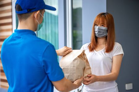 A young Asian deliveryman is delivering parcel to house her to sign to receive the product After she ordered online during the outbreak of the coronavirus or Covid-19 virus.