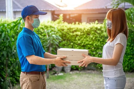 A young Asian deliveryman is delivering a package to customer in front of her house her to sign to receive the product After she ordered online during the outbreak of the coronavirus or Covid-19 virus. Stockfoto
