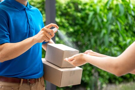 Asian deliveryman delivering package parcel food, spry the alcohol to her hand before get the box after she ordered online by application during the outbreak of the coronavirus or Covid-19 virus.