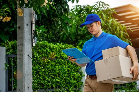 Asian delivery man in blue t-shirt carrying parcel box and document to sign in front of customer home. Delivery man concept.
