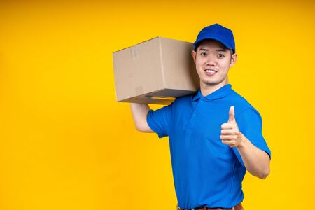 Asian delivery man in blue t-shirt carrying parcel box and show thumb up in front of customer home. Delivery man concept.