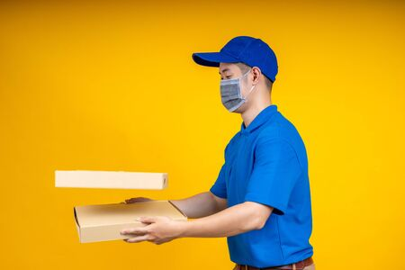 Young Asian delivery man holding food or pizza box and showing application on mobile over yellow isolate background. Work from home and delivery concept.