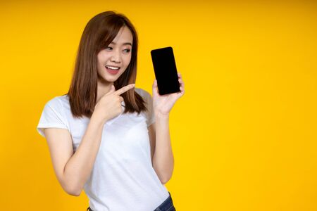 Young elegant Asian woman smiling and pointing to smartphone isolated on yellow background Imagens