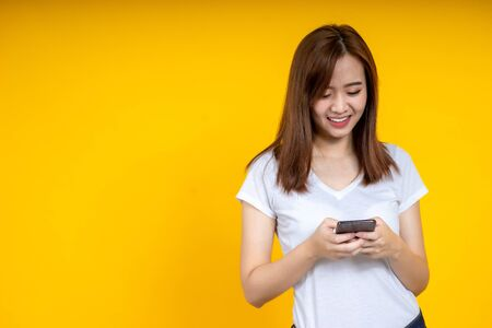 Young elegant Asian woman smiling and using chat or emailing on smartphone isolated on yellow background