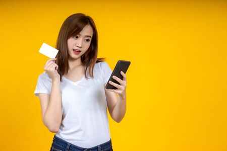 Young elegant Asian woman smiling and using smartphone and credit card to shopping online isolated on yellow background