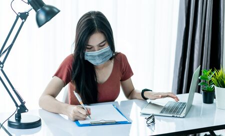 Asain woman wearing mark and using laptop, smarthphone and tablet to work from home and meeting online via internet with customer from home. Work from home or E-Learning concept. Foto de archivo