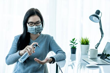 Asain woman cleaning hand and using laptop, smarthphone and tablet to work from home and meeting online via internet with customer from home. Work from home or E-Learning concept.