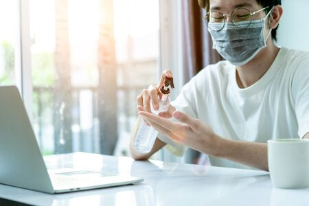 Asian man working from home, he use laptop and tablet and drinking coffee in covid-19 virus situation. Her working in quarantine for coronavirus. Work from home concept.