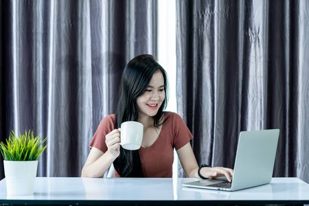 Asain woman drinking coffee and using laptop, smarthphone and tablet to work from home and meeting online via internet with customer from home. Work from home or E-Learning concept.