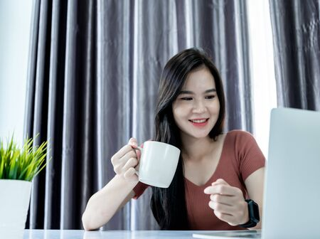 Asain woman using laptop, smarthphone and tablet to work from home and video call online via internet with customer from home. Cozy office workplace. Work from home or E-Learning concept.