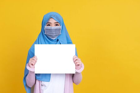 Islamic or muslim woman in hijab wearing mask protect covid-19 virus hiding behind white blank board over yellow isolated background with copy space. Standard-Bild