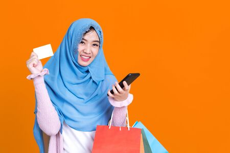 Photo of islamic woman in hijab headscarf wearing mask with oriental makeup use smartphone and credit card over orrange isolate background