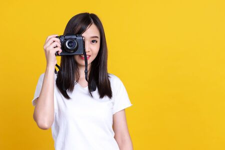 Portrait photo of Asian smiling pretty girl in white shirt taking photo on camera isolated over yellow background Standard-Bild