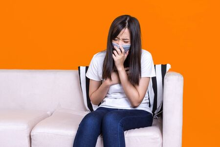 Asian woman sitting on sofa wearing protective face masks coughing or sneezing. Sick woman with flu wearing mask,feeling sick, coughing, wearing mask protection against flu. New coronavirus 2019.
