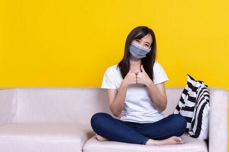 Asian woman sitting on sofa wearing face mask showing thumbup during Coronavirus or Covid-19 quarantine, coronavirus covid 19 infected patient in coronavirus quarantine over isolate yellow background