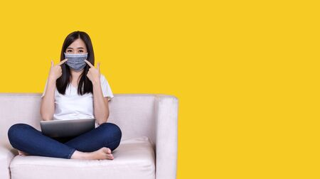 Asian woman sitting on sofa wearing face mask working from home during Coronavirus or Covid-19 quarantine, coronavirus covid 19 infected patient in coronavirus quarantine using computer Standard-Bild