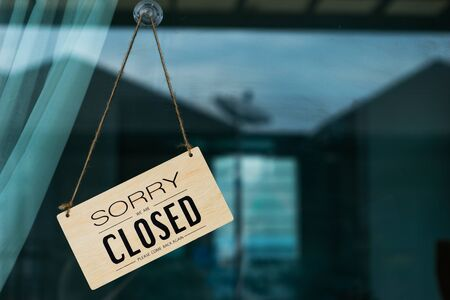Label 'Sorry we are closed please come back again' notice sign wood board hanging on door front coffee shop.