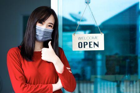 Asian woman shop owner smiling wearing medical face mask hanging label 'Welcom we are open' and showing thump up. She open her shop after pandemic of coronavirus outbreak