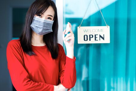 Asian woman shop owner smiling wearing medical face mask hanging label 'Welcom we are open' and showing alcohol bottle. She open her shop after pandemic of coronavirus outbreak