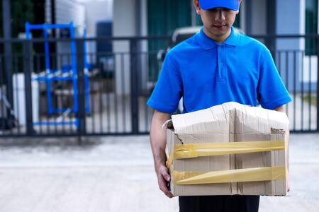 Asian delivery man in blue uniform he emotional falling courier courier showing damaged box, cheap parcel delivery, poor shipment quality. Standard-Bild
