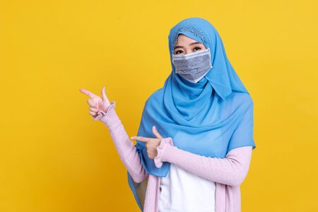 Asian muslim woman in medical mask Coronavirus pandemic disease pointing to copy space isolate background. COVID-19 virus epidemic outbreak.
