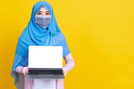 Asian muslim woman in medical mask Coronavirus pandemic disease using laptop computer isolate background. COVID-19 virus epidemic outbreak.