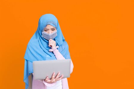 Asian muslim woman in medical mask Coronavirus pandemic disease using laptop computer and thinking isolate background. COVID-19 virus epidemic outbreak.