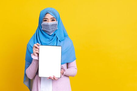 Asian muslim woman in medical mask Coronavirus pandemic disease showing tablet isolate background. COVID-19 virus epidemic outbreak.