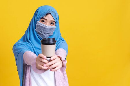Asian woman in medical mask showing coffee cup Coronavirus pandemic disease isolate background. COVID-19 virus epidemic outbreak.