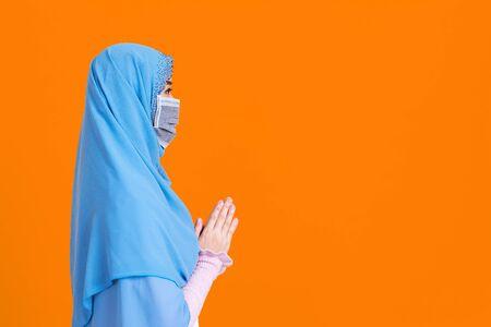 Side view of Asian woman in medical mask praying Coronavirus pandemic disease isolate background. COVID-19 virus epidemic outbreak.
