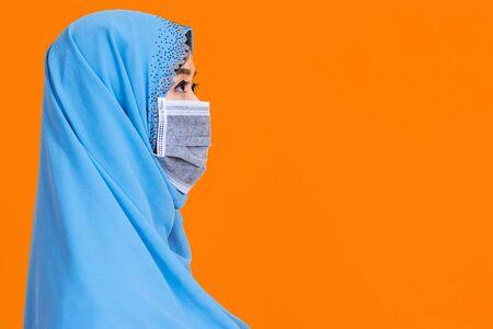 Side view of Asian woman in medical mask Coronavirus pandemic disease isolate background. COVID-19 virus epidemic outbreak. Standard-Bild