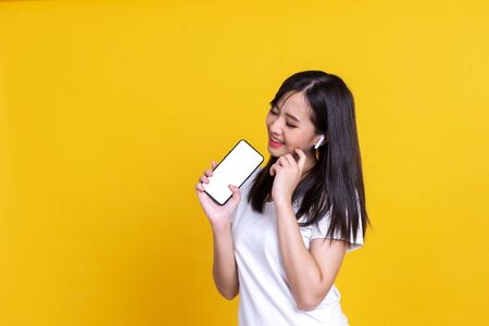 Happy Asian woman 20s listening to music via wireless earphones smiling and dancing isolated over background Standard-Bild