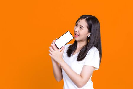 Happy Asian woman 20s singing while holding smartphone like microphone and listening to music via earphones isolated over background