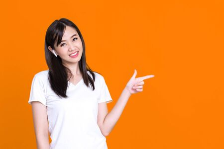Happy Asian woman 20s listening to music via wireless earphones smiling and pointing to copy space isolated over background