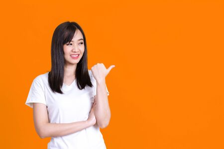 Beauty smiling brunette Asian woman pointing away and smiling and looking at the camera over color background