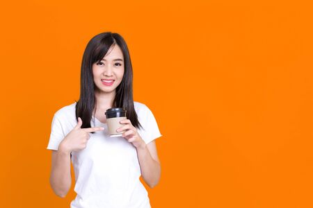 Asian woman hold paper cup hot coffee beverage have smiling break work process wear specs casual white shirt isolated color background Standard-Bild