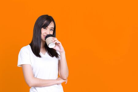 Portrait of Asian woman 20s smiling while drinking takeaway coffee or tea from paper cup isolated over background Standard-Bild