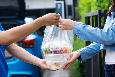 Asian delivery man delivering food, fruit, juice and vegetable to customer home - online grocery shopping service concept