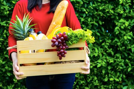 Asian woman holding wooden basket with vegetables. fresh vegetables in a basket. picnic in the garden. Stay at home. Enjoy cooking at home. Family concept.