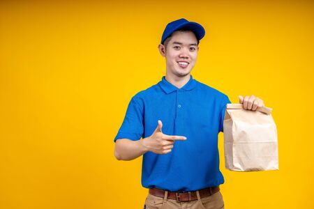 Asian delivery man holding fast food bag over yellow isolate background. Work from home and delivery concept.