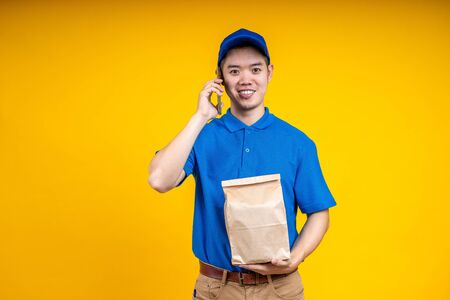 Asian delivery man holding fast food bag and using mobile phone over yellow isolate background. Work from home and delivery concept.