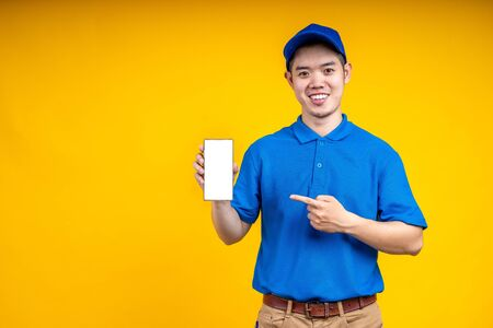 Asian delivery man pointer to application on mobile phone over yellow isolate background. Work from home and delivery concept. Standard-Bild